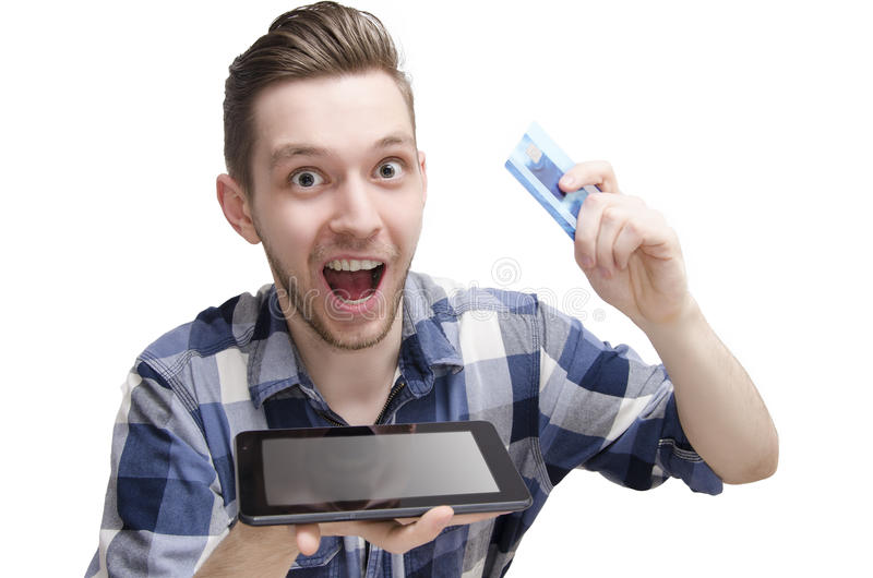 Exited young man, buying online via tablet, holding credit card in his hand. Young man booked ticket for travel via tablet, holding credit card and tablet in his stock photo