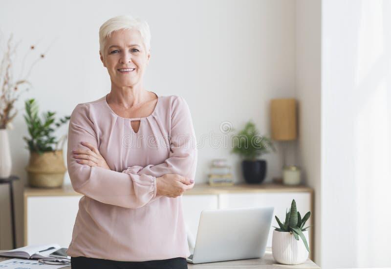 Exitosa anciana posando sobre el lugar de trabajo en casa imágenes de archivo libres de regalías
