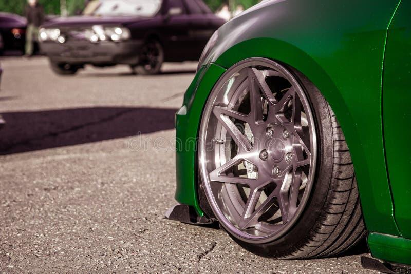 Exklusiv abgestimmte geschmiedete Räder auf einem in eine grüne Vinyl-Folie eingezogenen Fahrzeug Niedriges Auto mit Luftfederung stockfoto