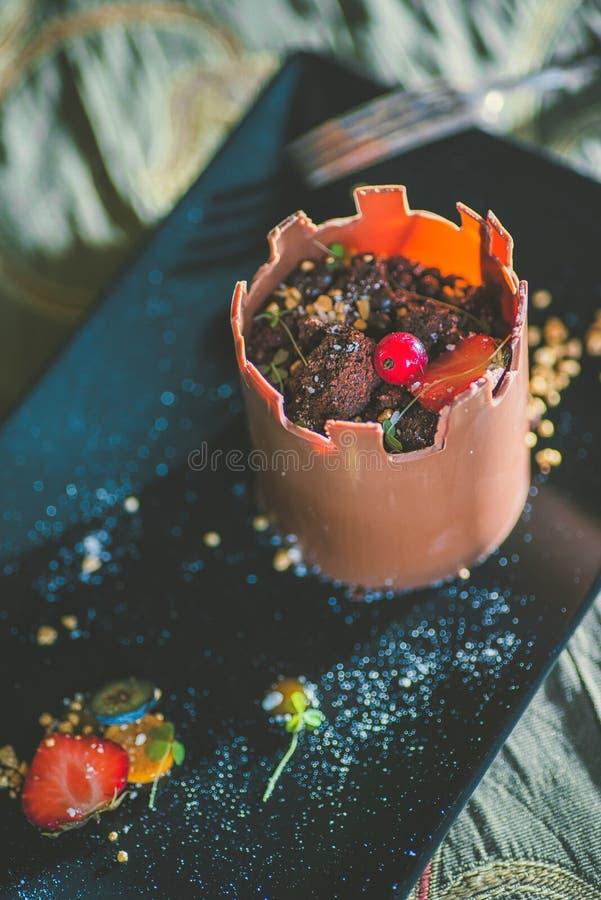 Exklusiver Schokoladenkuchen wie Turm mit Früchten diente auf Schwarzblech, Produktfotografie für Konditorei, Nachtisch für Schlo stockfoto