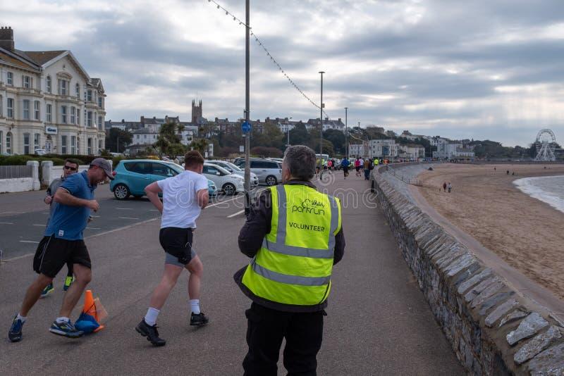 Exmouth, Devon, Reino Unido, abril, 13, 2019: Participação de corrida em um evento da corrida do parque ao longo da parte diantei imagens de stock royalty free