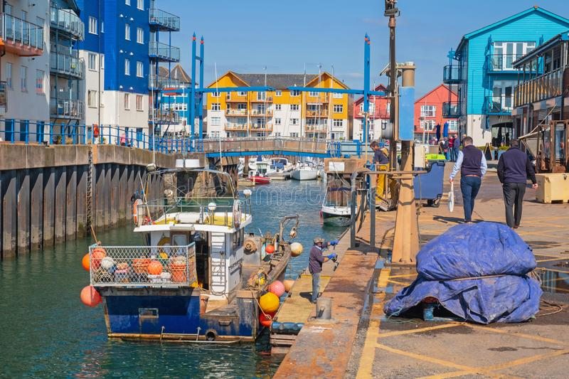 Fishing boat taking on provisions at the Exmouth quayside UK stock image
