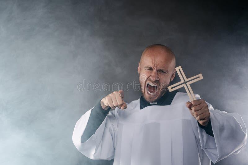 Exorcist för katolsk präst i den vita mässkjortan och svart skjorta royaltyfria foton