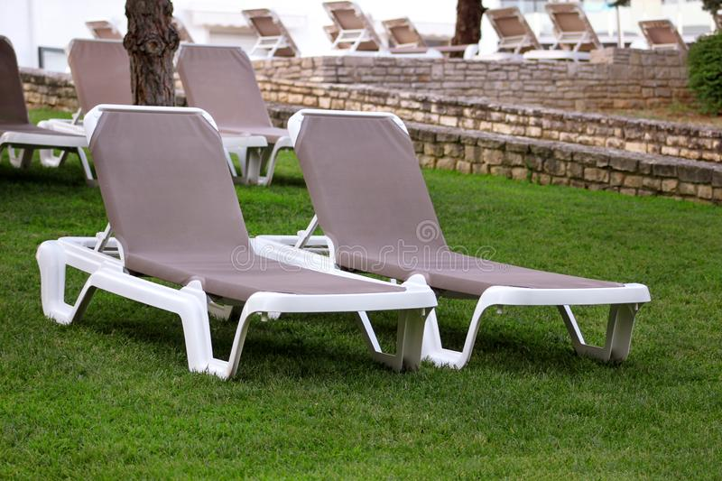 Exotic beach on mediterranean sea, sunbeds for sunbathing and relax on grass in tropical garden of luxury resort hotel. Sun loungers on lawn waiting for stock images