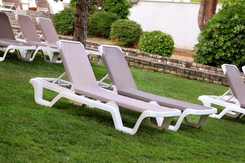 Exotic beach on mediterranean sea, sunbeds for sunbathing and relax on grass in tropical garden of luxury resort hotel. Sun loungers on lawn waiting for stock photos