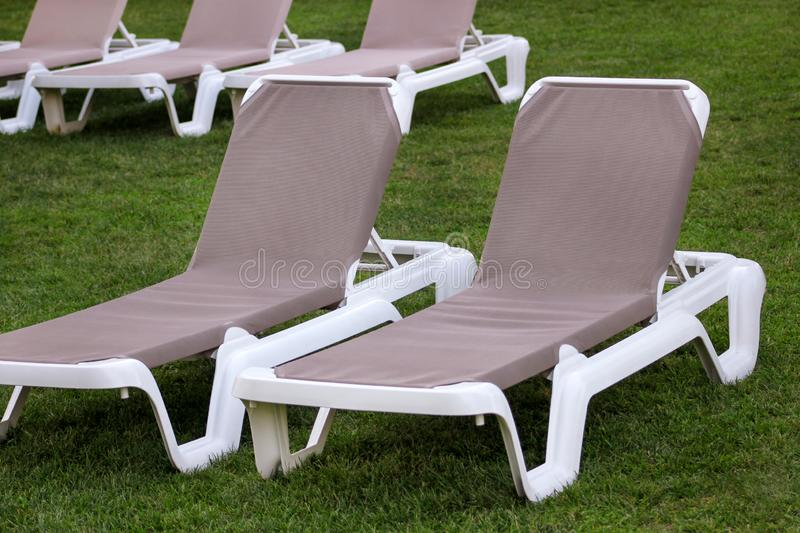 Exotic beach on mediterranean sea, sunbeds for sunbathing and relax on grass in tropical garden of luxury resort hotel. Sun loungers on lawn waiting for royalty free stock photo