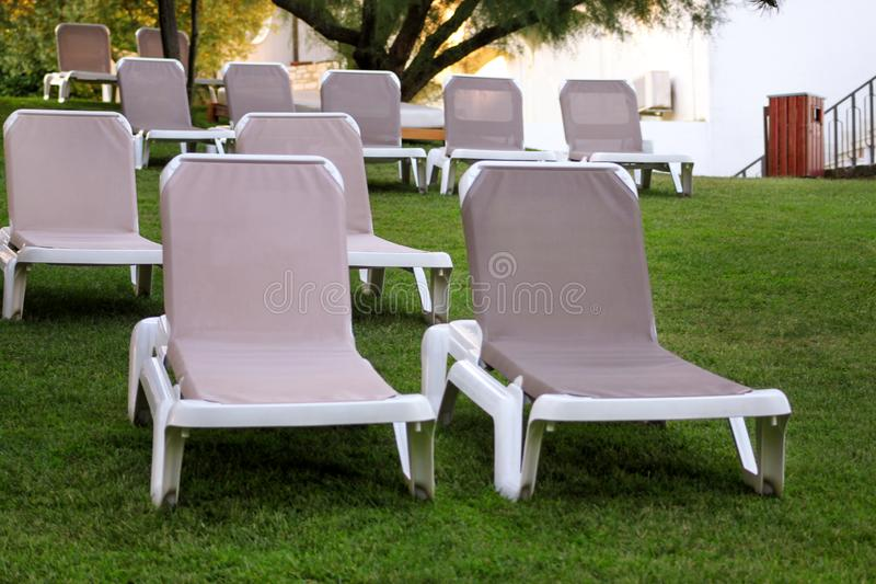 Exotic beach on mediterranean sea, sunbeds for sunbathing and relax on grass in tropical garden of luxury resort hotel. Sun loungers on lawn waiting for royalty free stock images
