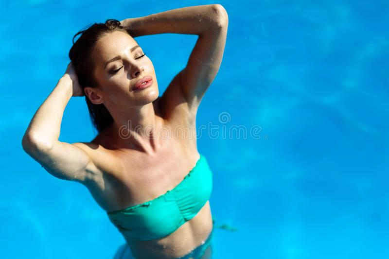 Exotic beautiful woman sunbathing and swimming stock photos