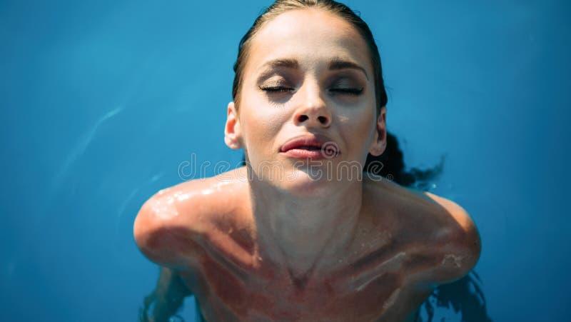 Exotic beautiful woman sunbathing and swimming royalty free stock photo