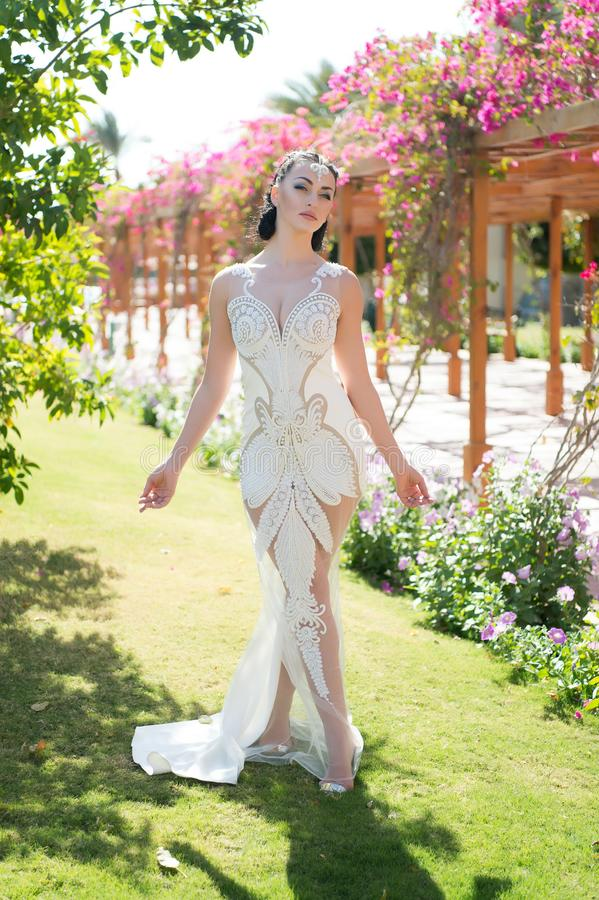 Exotic bride. Girl attractive expensive dress. Lady in luxury outfit walks exotic garden background. Woman make up stock photo
