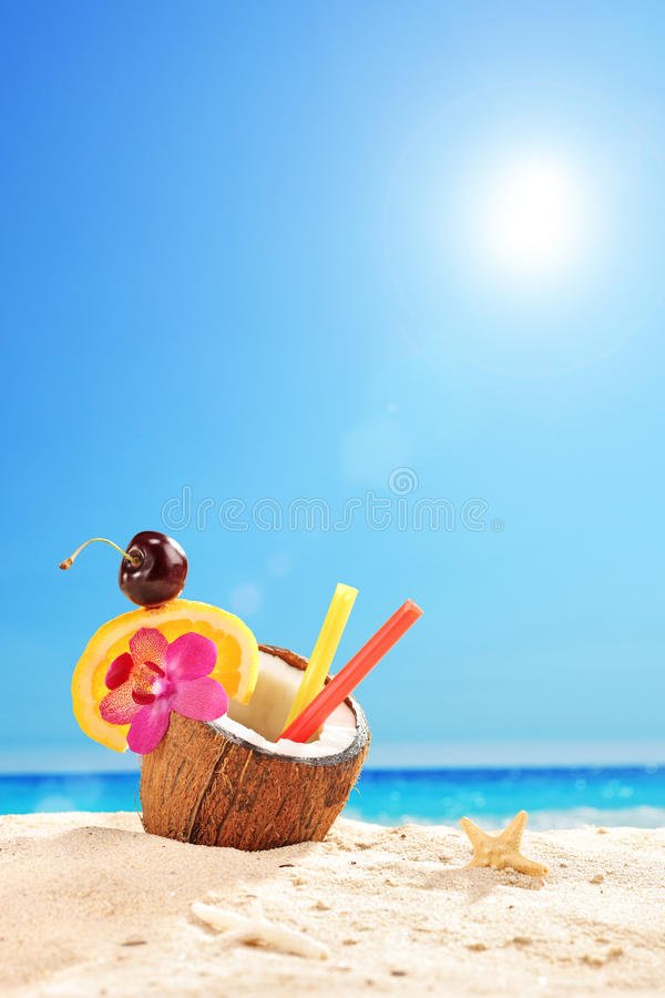 Exotic cocktail in a coconut on a tropical beach stock image