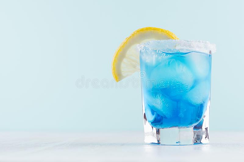 Exotic cold shot glass cocktail with blue curacao, ice cubes, salt rim, lemon slice on soft light mint color background. Exotic cold shot glass cocktail with royalty free stock photography