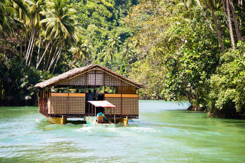 Exotic cruise boat with tourists on a jungle river. Island Bohol, Philippines. stock photo
