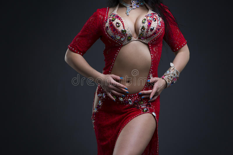 Exotic eastern women performs belly dance in ethnic red dress. Young beautiful exotic eastern woman performs belly dance in ethnic red dress on gray background royalty free stock images