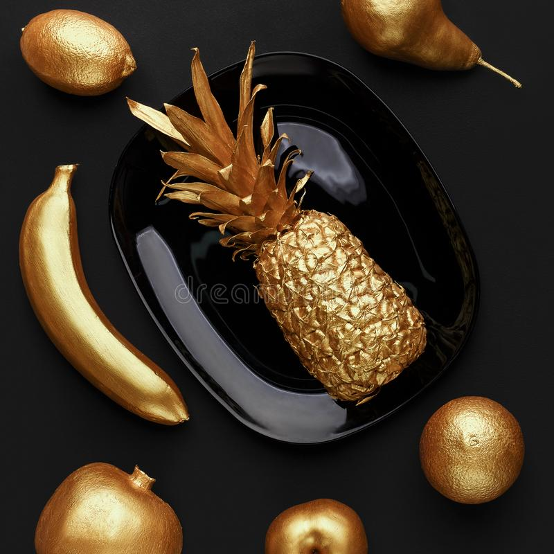 Exotic food concept. Golden fruits on plate over black background, top view. Exotic food concept stock photos