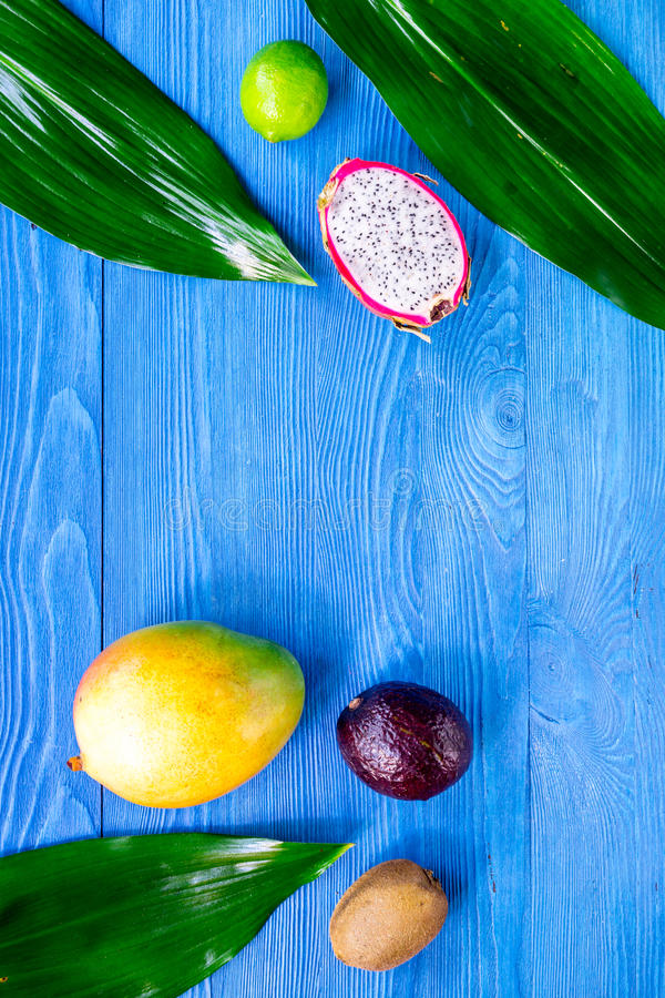 Exotic fruit meal. Dragonfruit, mangosteen, mango, kiwi, lime on blue wooden table background top view copyspace stock photography