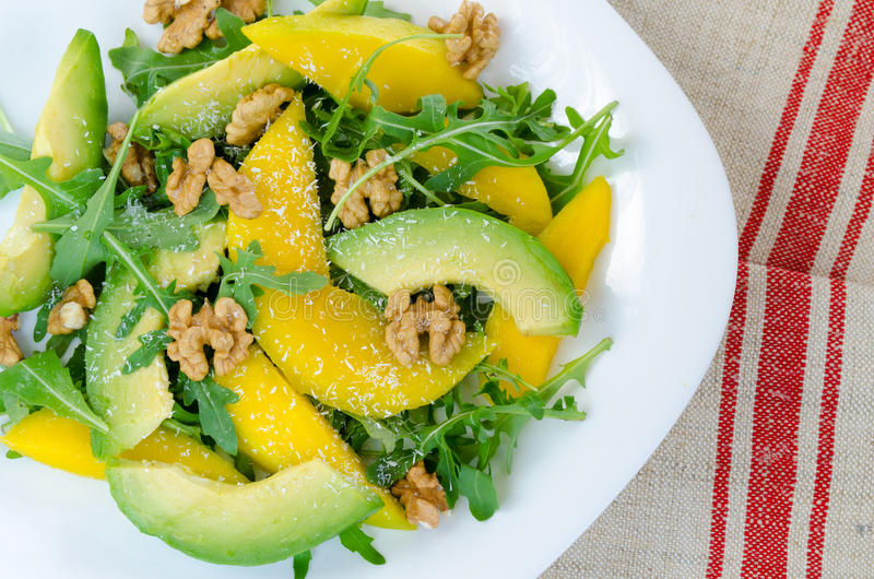 Exotic fruit salad food with mango, avocado, rucol. A and coconut topping royalty free stock photography