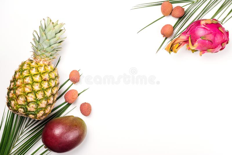 Exotic fruits on a white background, copy space. Pineapple, mango, dragon fruit, lychee. Top view of tropical fruits. Healthy food. Concept. Fresh fruit flat stock image