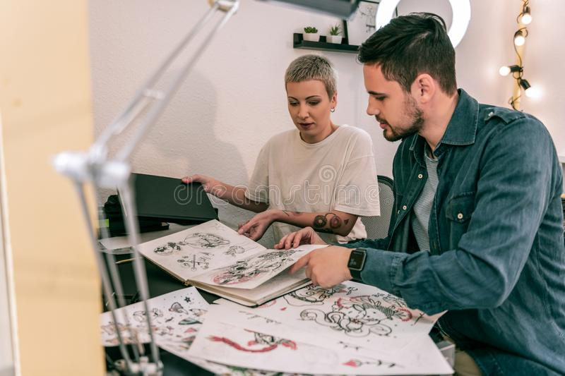 Professional female tattoo master showing all her sketches and designs. Exotic good-looking woman. Professional female tattoo master showing all her sketches and stock photography