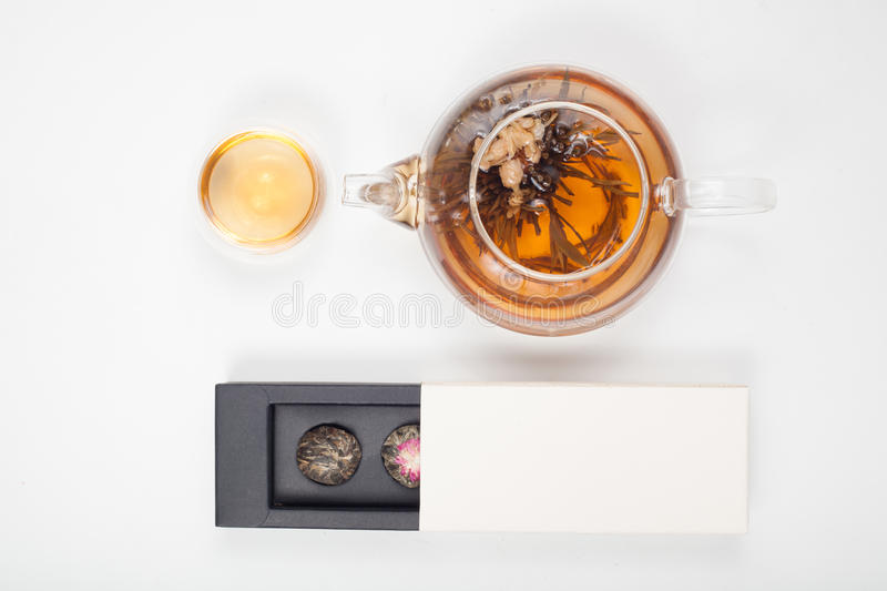 Exotic green tea with flowers in glass teapot and cup royalty free stock image