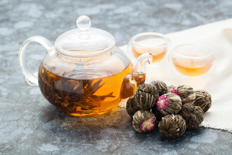 Exotic green tea with flowers in glass teapot royalty free stock photo