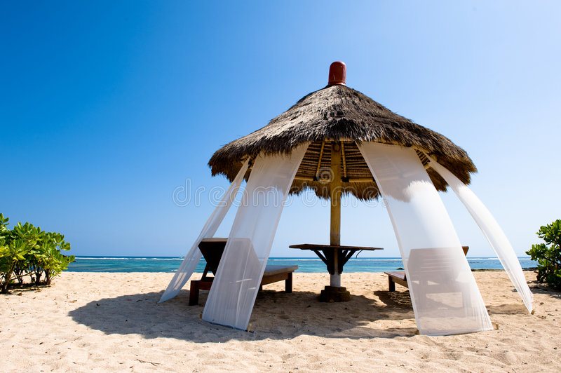 Exotic hut on tropical beach. Photo of an exotic hut on tropical beach royalty free stock image