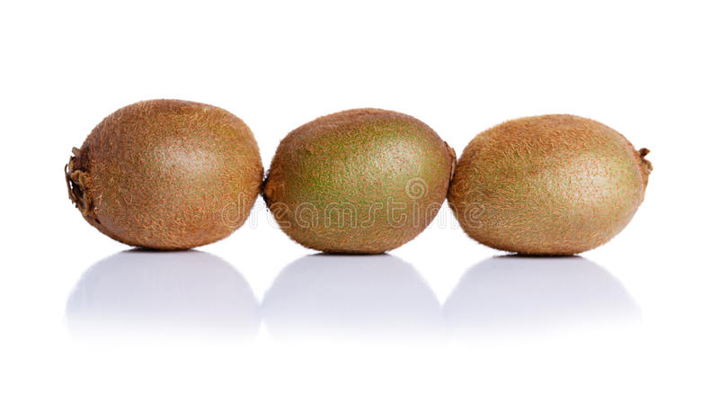 Exotic kiwi full of beneficial vitamins, isolated on a white background. Close-up of three whole kiwis fruit. stock photo