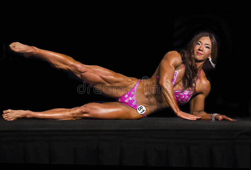Exotic Korean Physique Athlete Competes in Vancouver. Yeon Woo Ji of Korea displays an impressive muscularity, a developed and defined body, in the pro physique royalty free stock images