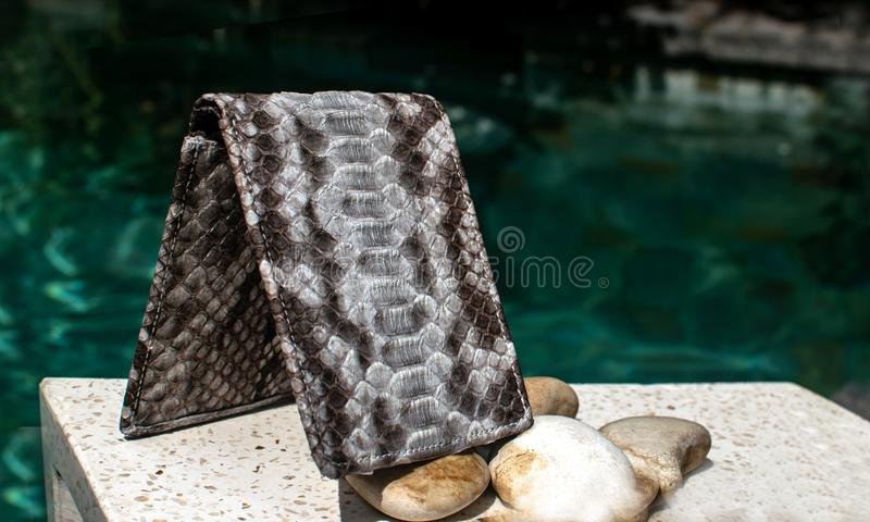 Exotic and luxury of hand made leather wallet, purse .Multi colored.Leather craft. On a stone tile with background with Plumeria. Exotic and luxury set of hand stock image