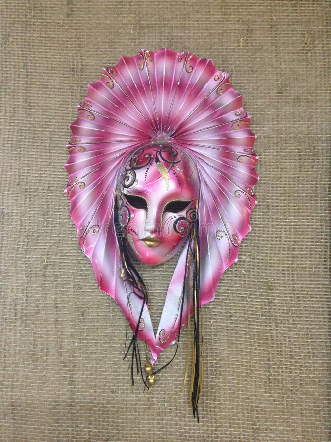 Exotic masquerade mask on burlap canvas. Pink mask with a big fan on the head and white-black-gold patterns stock image