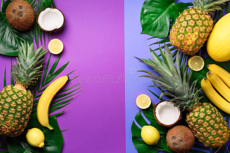 Exotic pineapples, coconuts, banana, melon, lemon, tropical palm and green monstera leaves on purple, violet background stock photo