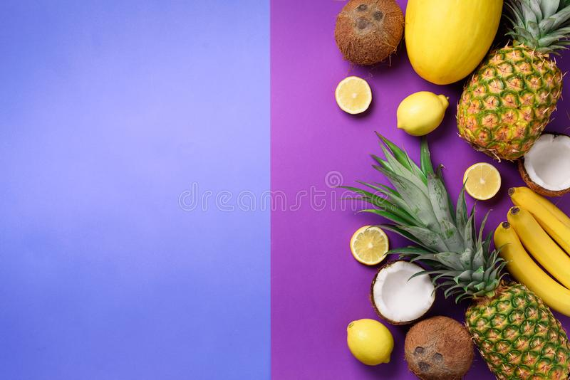 Exotic pineapples, coconuts, banana, melon, lemon, tropical palm and green monstera leaves on purple, violet background royalty free stock photos