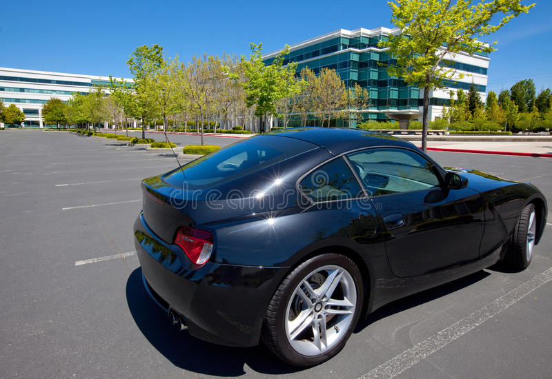 Exotic sports car in business park. Black metallic, exotic sports coupe, two seater sports car in empty parking lot of office business park royalty free stock image