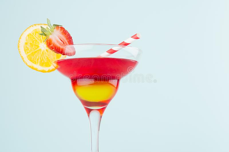 Exotic sunrise cocktail with red and yellow liquor, orange slice, strawberry, straw on soft light mint color background, details. Exotic sunrise cocktail with royalty free stock image