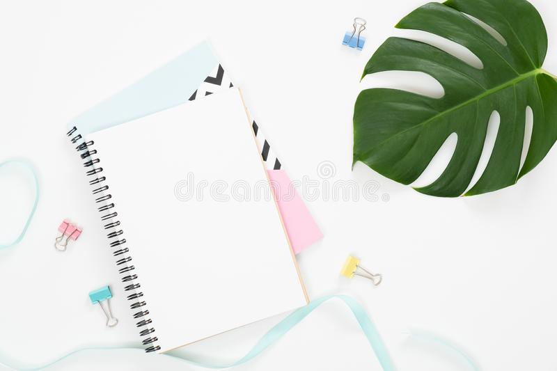 Exotic tropical monstera palm leaf and home office stationery, blank paper notepad on white background. Flat lay, top view minimal royalty free stock photo