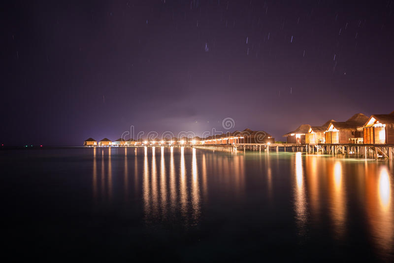 Exotic Tropical Paradise Over Water View Night Time Long Exposure. Over Water bungalow Night Time Long Exposure stock photos