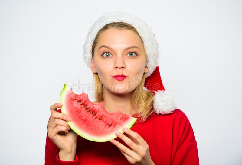 Exotic winter vacation. Celebrate new year exotic resort. Christmas girl eat watermelon. Girl santa hat eat watermelon. White background. Exotic christmas royalty free stock photos