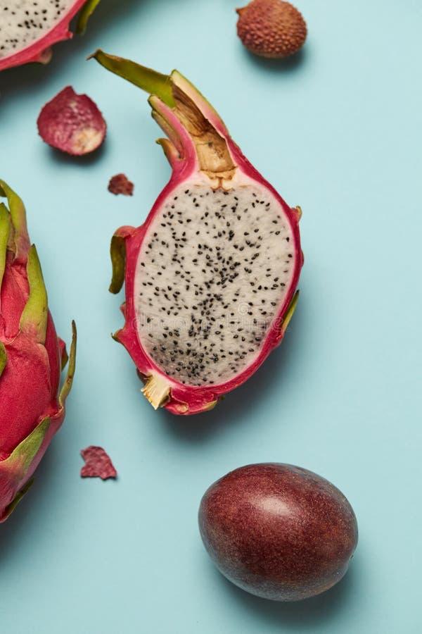 Exotisch half fruit Dragonfruit met roze en groene huid op blauwe achtergrond stock foto's