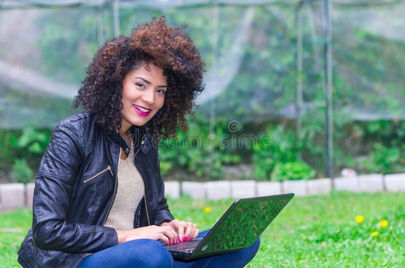 Exotisch mooi jong meisje die laptop in met behulp van stock fotografie