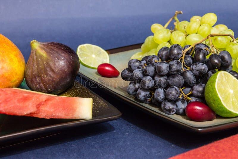 Exotisch vruchten verscheidenheidsstilleven met druiven, fig., kalk, perzik, mango en watermeloen stock afbeelding