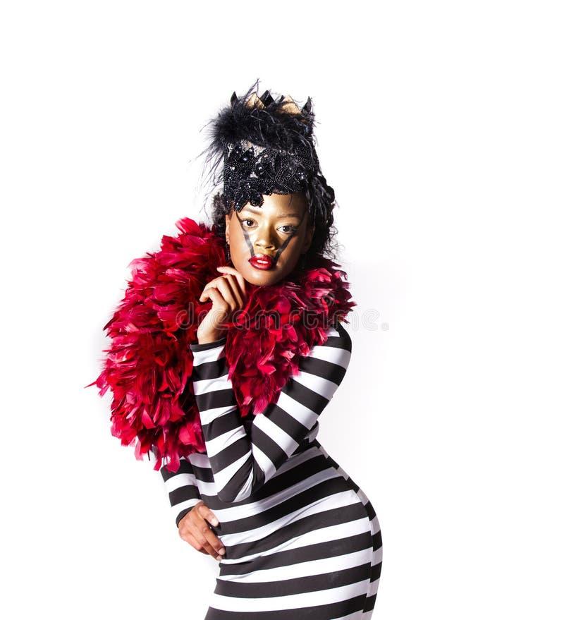 Exotische Frau, die rote Federn in Form eines Inneren trägt lizenzfreies stockfoto