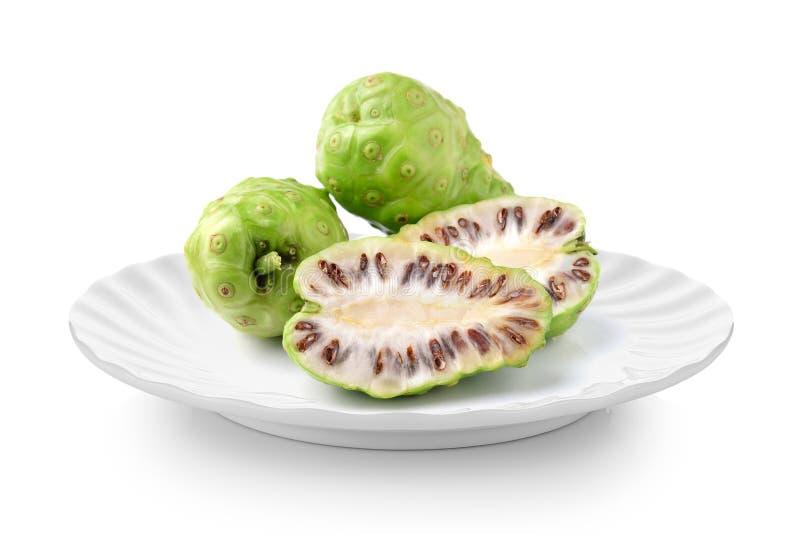 Exotische Frucht - Noni in der weißen Platte auf weißem Hintergrund lizenzfreies stockbild