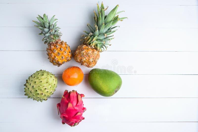 Exotische verse de zomervruchten op witte achtergrond Het draakfruit, ananas, dadelpruim, mango, annona cherimolavlakte lag stock foto's