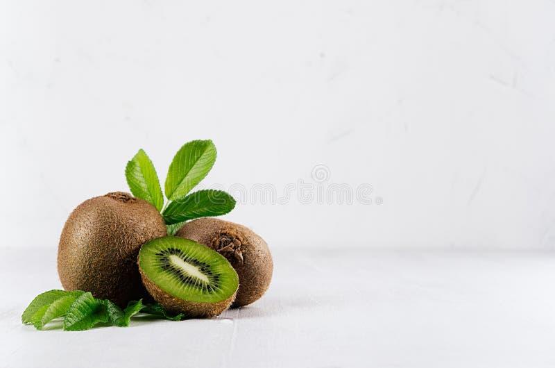 Exotische vruchten - sappige rijpe vlezige kiwi met plak, dalingssap en jonge groene bladeren in elegant wit keukenbinnenland royalty-vrije stock foto