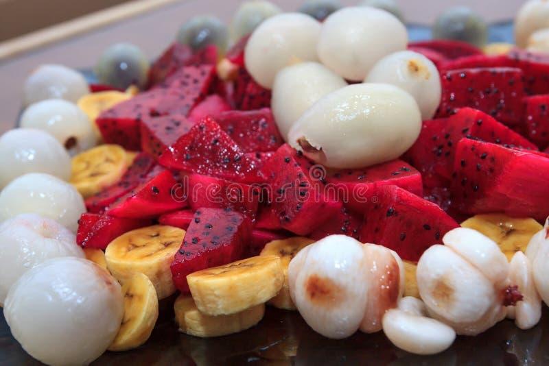Exotischer Fruchtsalat mit Dragon Fruit, pitahaya, Litschi, Mangostanfrucht, Banane und Rambutan auf blauer Glasplatte lizenzfreie stockbilder