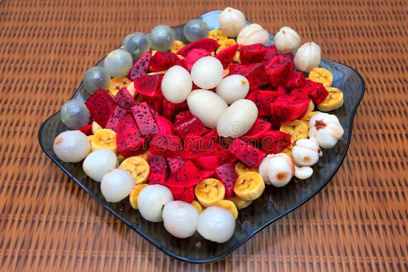 Exotischer Fruchtsalat mit Dragon Fruit, pitahaya, Litschi, Mangostanfrucht, Banane und Rambutan auf blauer Glasplatte stockfotografie