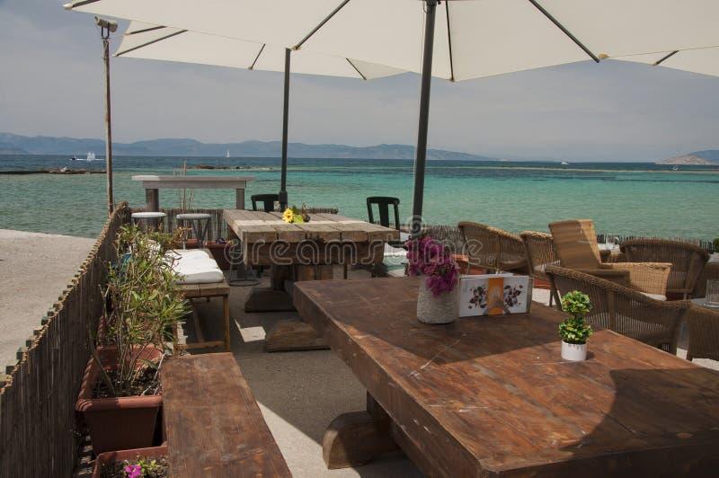 Exotisches Café mit der Ansicht des Türkiswassers an Aegina-Stadt stockbild