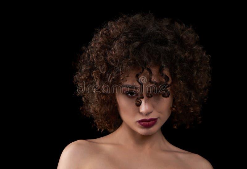 Exotisches gelocktes Mädchen, das Kamera betrachtet lizenzfreie stockbilder