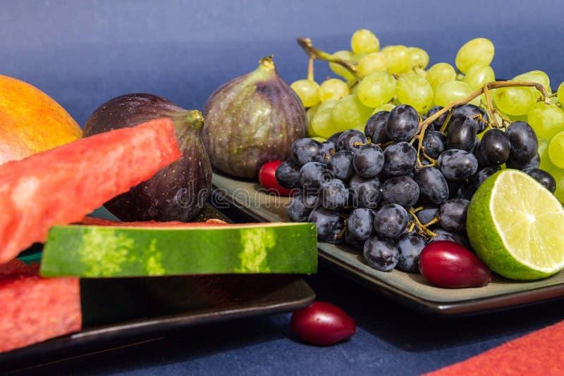 Exotisches Obstvielfaltstillleben mit Trauben, Feigen, Kalk, Pfirsich, Mango und Wassermelone lizenzfreies stockfoto