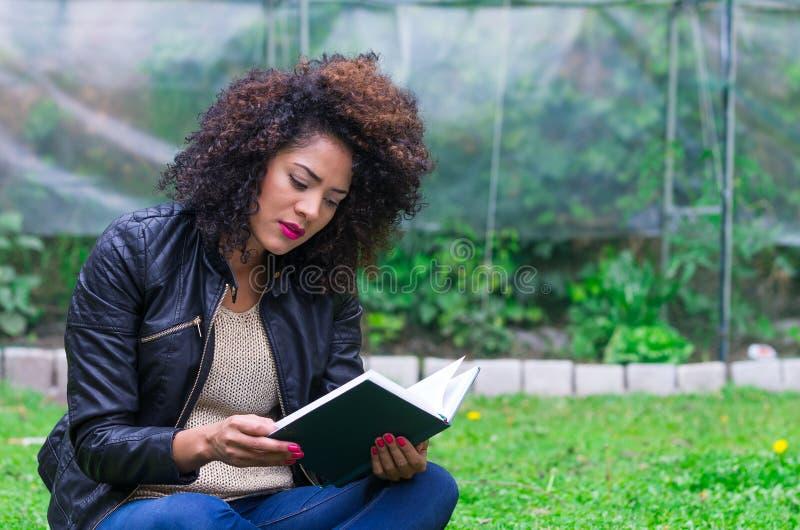 Exotisches schönes junges Mädchen, das im Garten sich entspannt stockfotografie